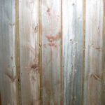 Close up of faded red wood reclaimed wood paneling